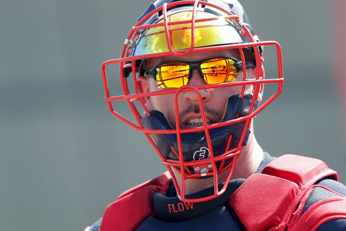 FILE - In this Feb. 13, 2020, file photo, Atlanta Braves catcher Tyler Flowers (25) watches during spring training baseball camp in North Port, Fla. The Braves are without their top two catchers, Tyler Flowers and Travis d'Árnaud, for Friday's opening game at the New York Mets after both players showed symptoms of the coronavirus.  (AP Photo/John Bazemore, File)