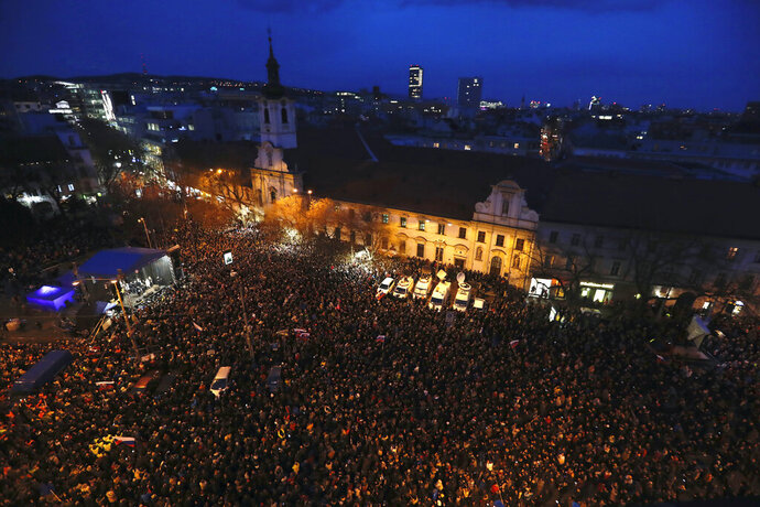 People gather on a square during a rally to mark one year anniversary of the slayings of an investigative reporter and his fiancee, in Bratislava, Slovakia, Thursday, Feb. 21, 2019.  Jan Kuciak and Martina Kusnirova were shot dead in their home on Feb. 21 last year. People used the anniversary on Thursday to press for the investigation to be completed. (AP Photo/Petr David Josek)