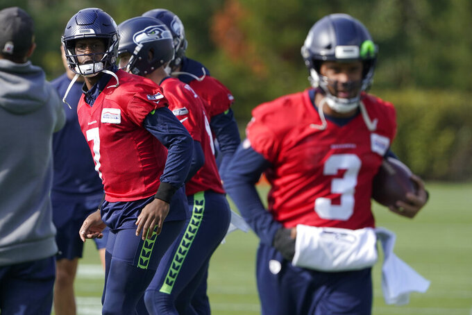 Seattle Seahawks quarterback Russell Wilson (3), keeps his injured hand in a pad as he runs through a warmup drill with backup quarterback Geno Smith (7) behind him during NFL football practice, Wednesday, Oct. 13, 2021, in Renton, Wash. Wilson had surgery on his hand last Friday, and Smith is expected to be the starting quarterback Sunday when the Seahawks play the Pittsburgh Steelers on the road. (AP Photo/Ted S. Warren)