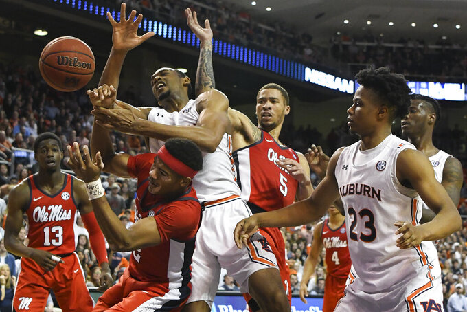 Auburn center Austin Wiley and Mississippi guard Devontae Shuler (2) vie for a rebound during the second half of an NCAA college basketball game Tuesday, Feb. 25, 2020, in Auburn, Ala. (AP Photo/Julie Bennett)