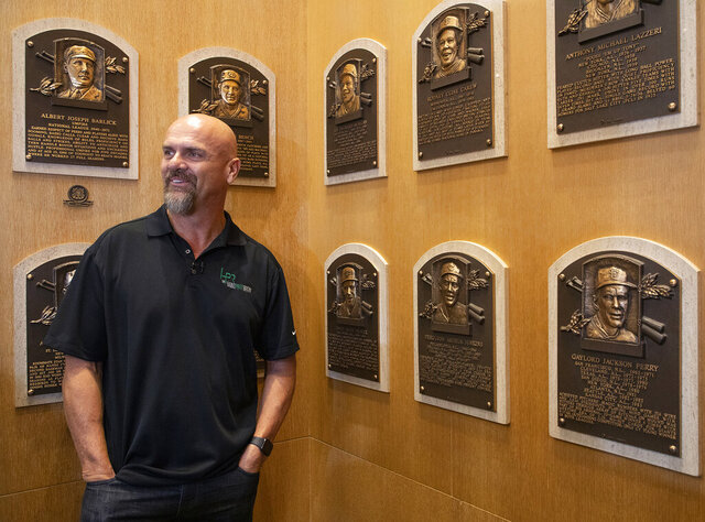In this photo provided by the National Baseball Hall of Fame and Museum, Larry Walker poses near the wall of plaques, Tuesday, Feb. 25, 2020 at the National Baseball Hall of Fame in Cooperstown, N.Y. Walker said on Tuesday that his Hall of Fame plaque will show him in Colorado Rockies cap, not a Montreal Expos hat. He added the key to picking the Rockies is that Colorado was