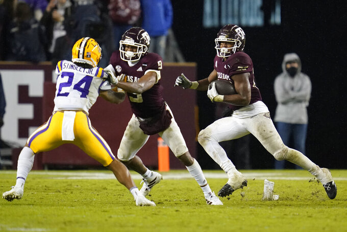 Texas A&M running back Isaiah Spiller (28) follows the block by wide receiver Hezekiah Jones (9) on LSU cornerback Derek Stingley Jr. (24) during the third quarter of an NCAA college football game Saturday, Nov. 28, 2020, in College Station, Texas. (AP Photo/Sam Craft)