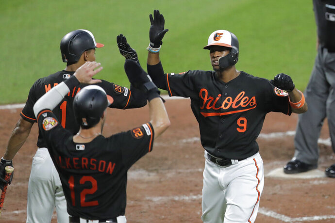 Baltimore Orioles' Keon Broxton (9) is greeted near home plate by Richie Martin (1) and Stevie Wilkerson after hitting a two-run home run off Boston Red Sox starting pitcher David Price during the fourth inning of a baseball game Friday, July 19, 2019, in Baltimore. The Orioles won 11-2. (AP Photo/Julio Cortez)