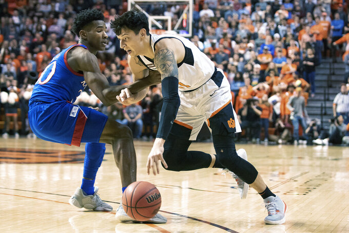 Kansas guard Ochai Agbaji (30) attempts to stop Oklahoma State guard Lindy Waters III (21) during the first half of an NCAA college basketball game in Stillwater, Okla., Monday, Jan. 27, 2020. (AP Photo/Brody Schmidt)