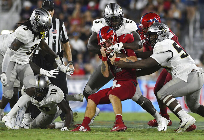Florida Atlantic quarterback Chris Robison (2) gets tackled by Central Florida defensive lineman Randy Charlton (5) after a short gain during an NCAA college football game Saturday, Sept. 7, 2019, in Boca Raton, Fla. (AP Photo/Jim Rassol)