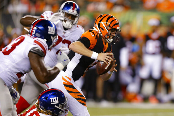 Cincinnati Bengals quarterback Ryan Finley (5) tries to get away from a trio of New York Giants during the second half of an NFL preseason football game Thursday, Aug. 22, 2019, in Cincinnati. (AP Photo/Gary Landers)