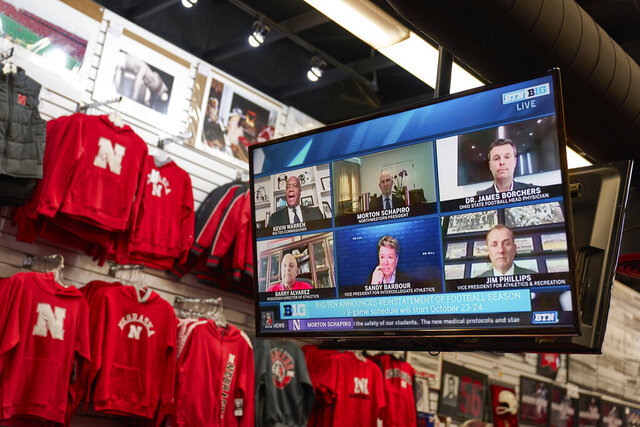 The Husker Hounds sports apparel store in Omaha, Neb., shows on television screens Wednesday, Sept. 16, 2020, a Big Ten virtual news conference to discuss the reopening of the football season. President Donald Trump was quick to spike the ball in celebration when the Big Ten announced the return of fall football at colleges clustered in some of the Midwest battleground states critical to his reelection effort. (AP Photo/Nati Harnik)