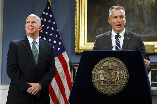 FILE - In this Monday, Nov. 4, 2019, file photo, New York City Police Commissioner James O'Neill, left, listens as his successor, Chief of Detectives Dermot Shea speaks at New York's City Hall. Shea succeeds O'Neill on Sunday, Dec. 1, 2019, as commissioner of the New York Police Department. The 62-year-old O'Neill is retiring after 36 years with the department, the last three as commissioner. (AP Photo/Richard Drew, File)