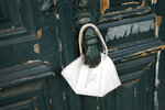 A face mask hangs from a door knocker in Lisbon, Saturday, Sept. 25, 2021. Portugal is scrapping many of its remaining COVID-19 restrictions, after becoming the world leader in the vaccination rollout, but the wearing of face masks will still be mandatory on public transport, in hospitals and care homes, and in shopping malls. (AP Photo/Armando Franca)