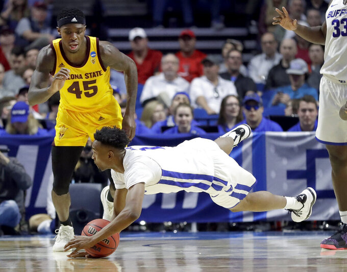 Buffalo's Montell McRae, bottom, dives after a loose ball as Arizona State's Zylan Cheatham (45) watches during the first half of a first round men's college basketball game in the NCAA Tournament Friday, March 22, 2019, in Tulsa, Okla. (AP Photo/Jeff Roberson)