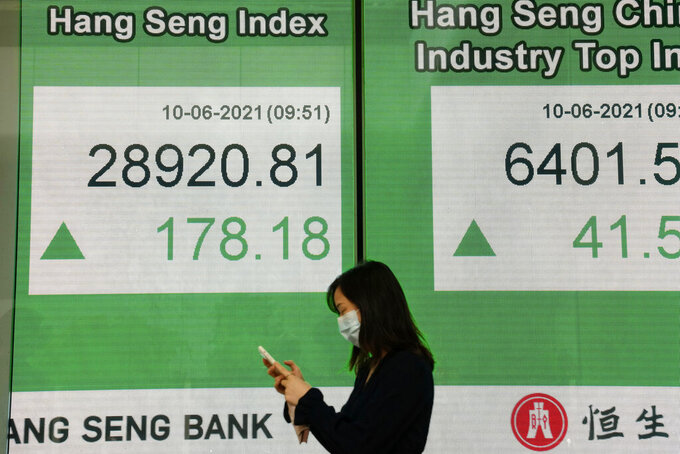 A woman wearing a face mask walks past a bank's electronic board showing the Hong Kong share index in Hong Kong, Thursday, June 10, 2021. Asian shares are higher after Wall Street logged modest losses, as investors await key U.S. inflation data. Benchmarks rose across the region, but stayed in a narrow range. (AP Photo/Kin Cheung)