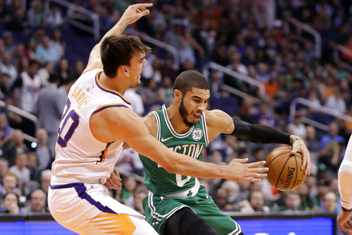 Boston Celtics forward Jayson Tatum, right, backs down Phoenix Suns forward Dario Saric, left, during the first half of an NBA basketball game, Monday, Nov. 18, 2019, in Phoenix. (AP Photo/Matt York)