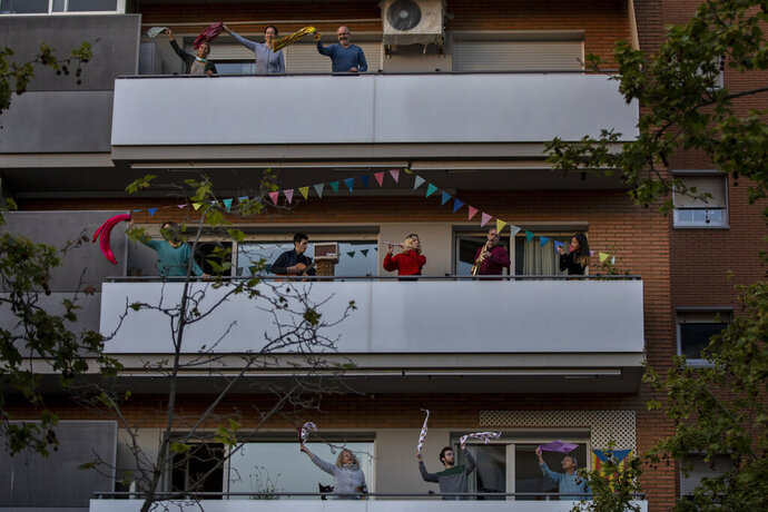 People play instruments as other dance on their balconies in support of the medical staff that are working on the COVID-19 virus outbreak in Barcelona, Spain, Sunday, April 5, 2020. Spanish Prime Minister Pedro Sanchez announced that he would ask the Parliament to extend the state of emergency by two more weeks, taking the lockdown on mobility until April 26. The new coronavirus causes mild or moderate symptoms for most people, but for some, especially older adults and people with existing health problems, it can cause more severe illness or death. (AP Photo/Emilio Morenatti)