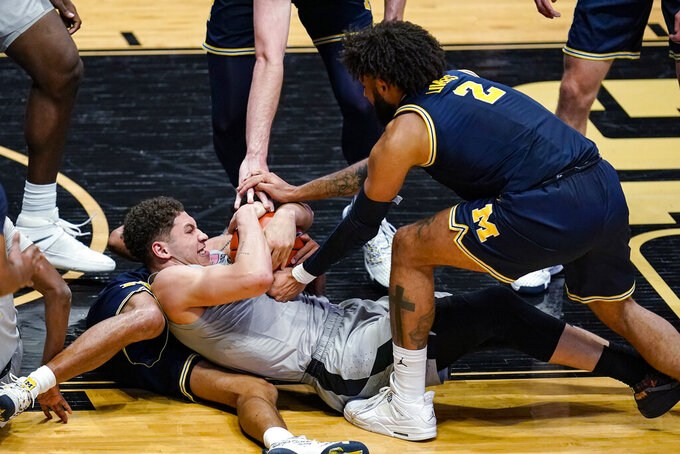 Purdue forward Mason Gillis (0) and Michigan forward Isaiah Livers (2) try to get possession of the ball during the second half of an NCAA college basketball game in West Lafayette, Ind., Friday, Jan. 22, 2021. (AP Photo/Michael Conroy)