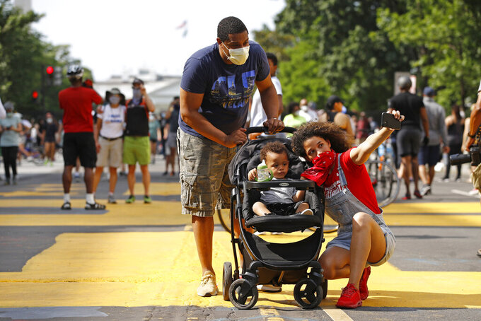 Katie Williams, right, poses for a photo with her son Benjamin, 18 months, and husband Kyle near the White House, Saturday, June 6, 2020, in Washington, as people gather before scheduled protests over the death of George Floyd, who died after being restrained by Minneapolis police officers. (AP Photo/Patrick Semansky)