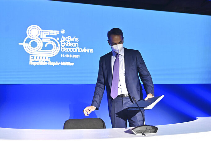 Greece's Prime Minister Kyriakos Mitsotakis takes his seat for a news conference at the Thessaloniki International Fair, in the northern city of Thessaloniki, Greece, Sunday, Sept. 12, 2021. Greece's economy will grow 5.9% during 2021, far more than the original 3.6% estimate, Prime Minister Kyriakos Mitsotakis announced Saturday. (AP Photo/Giannis Papanikos)