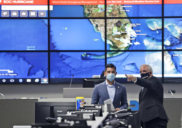 Miami-Dade County Mayor Carlos Gimenez, right, gives a tour to Acting Secretary of Homeland Security, Chad Wolf, of the Miami-Dade Emergency Operations Center, Monday, June 8, 2020, in Doral, Fla. Wolf, who also toured the National Hurricane Center, spoke during a news conference on the on DHS's operational readiness for the hurricane season. (AP Photo/Wilfredo Lee)