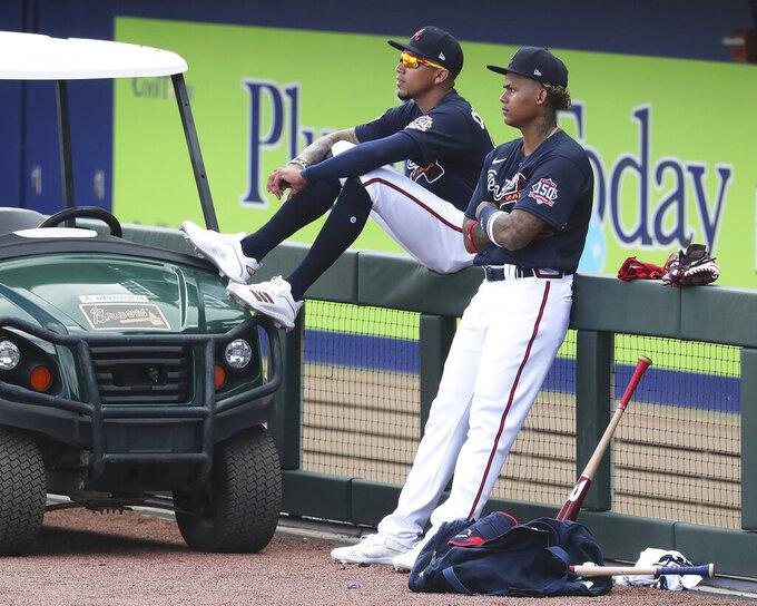 Atlanta Braves infielder Johan Camargo, left, and outfielder Cristian Pache watch spring training baseball practice in North Port, Fla., Wednesday, Feb. 24, 2021. (Curtis Compton/Atlanta Journal-Constitution via AP)