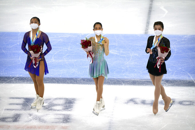 From left, women's singles silver medalist Kaori Sakamoto of Japan, gold medalist Mai Mihara of Japan, and bronze medalist Joanna So of Hong Kong pose on the ice during their medal ceremony at the Asian Open Figure Skating Trophy, a test event for the 2022 Winter Olympics, at the Capital Indoor Stadium in Beijing, Friday, Oct. 15, 2021. (AP Photo/Mark Schiefelbein)