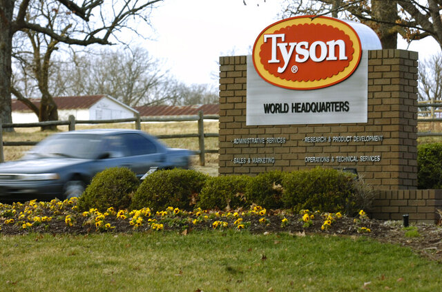 FILE - In this Jan. 29, 2006, file photo, a car passes in front of a Tyson Foods Inc., sign at Tyson headquarters in Springdale, Ark.  Tyson Foods plans to administer thousands of coronavirus tests per week at its U.S. facilities under an expanded effort to protect workers and keep plants running. The Springdale, Arkansas-based company, which processes about 20% of all beef, pork and chicken in the U.S., on Wednesday, July 29, 2020, said it will randomly test employees who have no symptoms as well as those with symptoms   (AP Photo/April L. Brown, File)