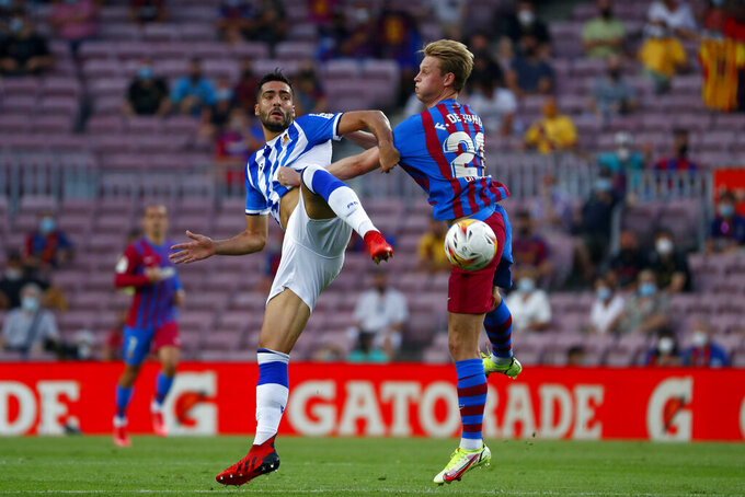 Real Sociedad's Mikel Merino vies for the ball with Barcelona's Frenkie de Jong, right, during a Spanish La Liga soccer match between Barcelona and Real Sociedad at Camp Nou stadium in Barcelona, Spain, Sunday, Aug. 15, 2021. (AP Photo/Joan Monfort)