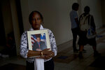 """In this Sept. 4, 2018 photo, Gloria Rosado Ortiz poses with an image of her late husband Ernesto Curiel in San Juan, Puerto Rico. Curiel, a 60-year-old who had heart problems and diabetes, walked 10 flights of stairs to the ground floor of his condominium, twice a day, to get insulin from a refrigerator cooled by a generator after Hurricane Maria hit. On Oct. 29, he died of a heart attack. Rosado applied to FEMA in Nov. 2017 for financial aid to defray $4,000 in funeral costs, and was told it was going to take some time due to the large number of applications following the rise in the official death toll. """"He was in a fragile state, but not so fragile that he'd only last a month after the hurricane,"""" said Ortiz. (AP Photo/Ramon Espinosa)"""