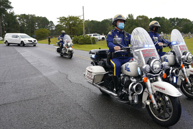 A Louisiana State Police motorcycle honor guard precedes the hearse carrying the body of Master Trooper Chris Hollingsworth, Friday, Sept. 25, 2020, in West Monroe, La. Hollingsworth, killed in a car crash hours after he was told he would be fired for his role in the death of a Black man, was buried with honors Friday at a ceremony that authorities sought to keep secret out of concerns it would attract a mass protest. (AP Photo/Rogelio V. Solis)