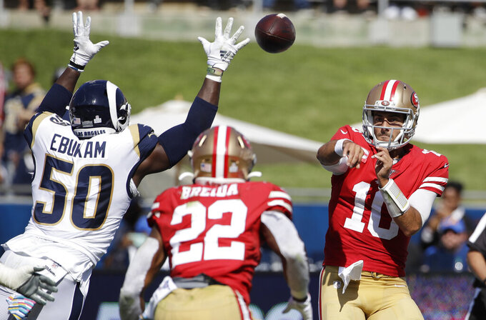San Francisco 49ers quarterback Jimmy Garoppolo (10) throws to running back Matt Breida (22) as Los Angeles Rams outside linebacker Samson Ebukam (50) defends during the first half of an NFL football game Sunday, Oct. 13, 2019, in Los Angeles. (AP Photo/Alex Gallardo)