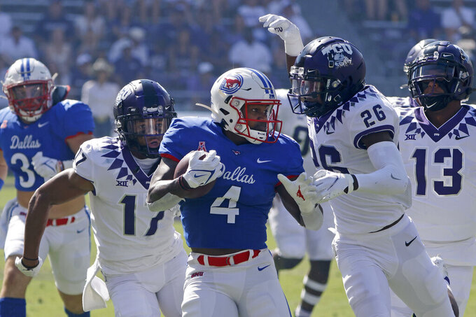 SMU running back Tre Siggers (4) finishes a long run as he is chased by TCU safeties Deshawn McCuin (17) and Christian McDonald (26) during the first half of an NCAA college football game in Fort Worth,Texas, Saturday, Sept. 25, 2021. (AP Photo/Michael Ainsworth)