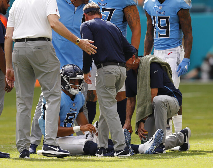 FILE - In this Sept. 9, 2018 file photo Tennessee Titans quarterback Marcus Mariota (8) is attended on the field, during the second half of an NFL football game against the Miami Dolphins in Miami Gardens, Fla. Mariota practiced fully Wednesday, Sept. 12, 2018 after being knocked out of Tennessee's season opener after hurting the elbow on his throwing arm. (AP Photo/Brynn Anderson, file)