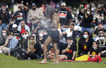 An Aboriginal man carries a small fire during a traditional smoking ceremony as thousands gather at a rally supporting the Black Lives Matter and Black Deaths in Custody movements in Sydney, Sunday, July 5, 2020. (AP Photo/Rick Rycroft)