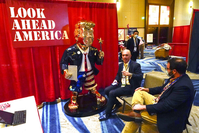 FILE - In this Feb. 26, 2021, file photo, Look Ahead America sponsor Matt Braynard, center, talks to conference attendees at his booth in the merchandise show with a statue of former president Donald Trump at the Conservative Political Action Conference (CPAC) in Orlando, Fla. (AP Photo/John Raoux, File)