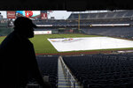 A worker looks at the tarp covering the field before a baseball game between the Washington Nationals and the San Francisco Giants at Nationals Park, Thursday, June 10, 2021, in Washington. The game was postponed until Saturday June 12th. (AP Photo/Alex Brandon)