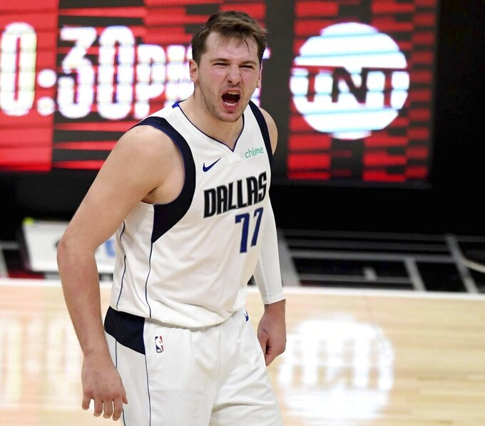 Luka Doncic #77 of the Dallas Mavericks reacts after teammate Kristaps Porzingis (not pictured) scores on a three pointer against the LA Clippers in the fourth quarter of game five of the Western Conference First Round NBA Playoff basketball game at the Staples Center in Los Angeles on Wednesday, June 2, 2021. Dallas Mavericks won 105-100. (Keith Birmingham/The Orange County Register via AP)/The Orange County Register via AP)
