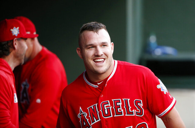 "FILE - In this April 15, 2019, file photo, Los Angeles Angels designated hitter Mike Trout smiles in the dugout after he scored on a home run by Brian Goodwin against the Texas Rangers during the first inning of a baseball game in Arlington, Texas. If Major League Baseball and the players' union can partially save its 2020 season, the potential 60-to 70-game season would be much shorter than the usual 162-game grind. It would look much more like a college baseball season. ""If there's 60 games on the schedule, someone like Mike Trout is going to play 60 games,"" former major league baseball player and college coach Tracy Woodson said. (AP Photo/Michael Ainsworth, File)"