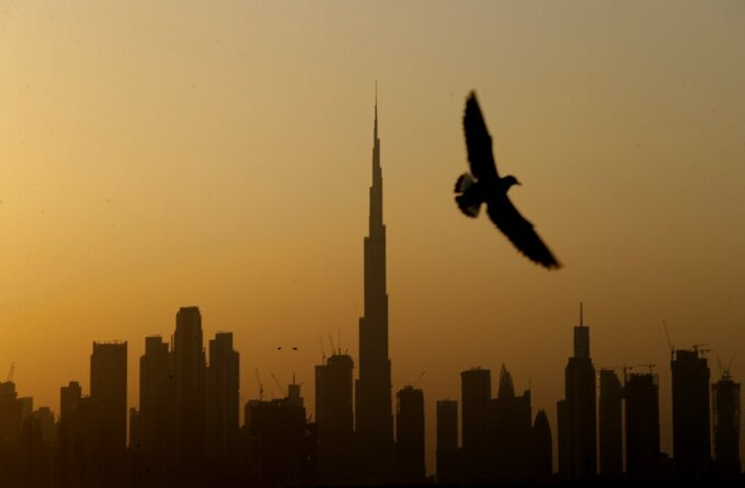 A seagull flies pass the view of city skyline and the world tallest tower, Burj Khalifa, in Dubai, United Arab Emirates, Friday, Jan.29, 2021. (AP Photo/Kamran Jebreili)