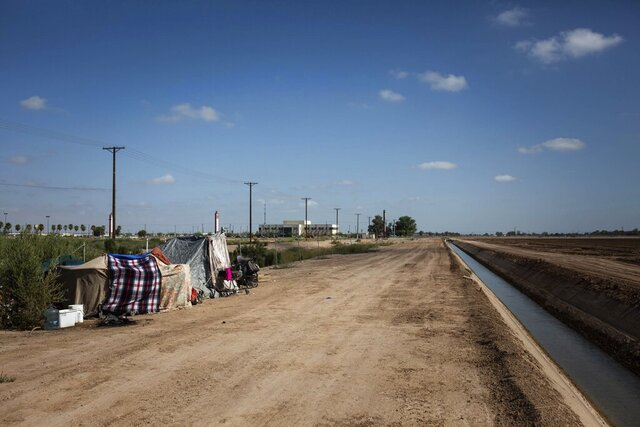 This July 24, 2020, photo shows a homeless encampment near a canal in El Centro, Calif. As support services have dwindled amid the COVID-19 pandemic, some homeless people in Imperial County have resorted to bathing in irrigation canals. Homelessness looks different in different parts of the U.S., especially in rural agricultural regions such as Imperial County. (Anna Maria Barry-Jester/KHN and the Howard Center For Investigative Journalism via AP)