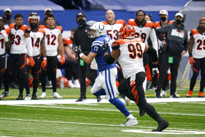 Indianapolis Colts quarterback Philip Rivers (17) runs from Cincinnati Bengals' Christian Covington (99) during the second half of an NFL football game, Sunday, Oct. 18, 2020, in Indianapolis. (AP Photo/Michael Conroy)