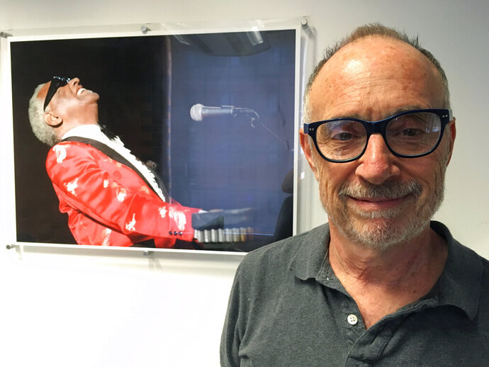 FILE - In this June 18, 2018, file photo, Gregory Katz, acting London bureau chief for The Associated Press, poses for a photo backdropped by a photo of American pianist singer songwriter Ray Charles, at the AP's London office. Katz, an acclaimed correspondent for The AP whose career over four decades took him across the globe, died Monday, June 22, 2020. He had been ill in recent months and had contracted COVID-19. He was 67. (AP Photo/File)