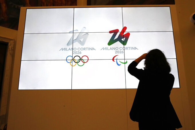 "The logo of 2026 Milan-Cortina Olympics and Paralympics, right, are unveiled to the journalists at a press conference in Rome, Tuesday, March 30, 2021. A futuristic white-on-white logo was unveiled as the emblem for the 2026 Milan-Cortina Olympics on Tuesday following an online vote. Nearly a million votes were cast, 871,566 to be exact, over the last two weeks from Italy and 168 other nations for the two finalists. The ""Futura"" logo received 75 percent of the votes, winning easily ahead of the more traditional ""Dado"" option. (AP Photo/Alessandra Tarantino)"