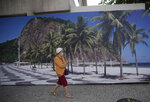 A woman walks past a landscape photo of Leme beach outside the closed Hilton hotel in Rio de Janeiro, Brazil, Wednesday, Aug. 26, 2020. Other hotel operators are offering hotel rooms for office space, aimed at enticing workers who need a home office without distractions, hoping to offset the sharp decline in tourist revenue due to the new coronavirus pandemic. (AP Photo/Silvia Izquierdo)