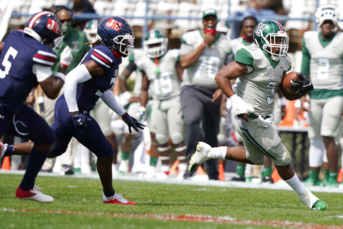 Mississippi Valley State running back Caleb Johnson runs from Jackson State pursuers during the first half of an NCAA college football game, Sunday, March 14, 2021, in Jackson, Miss. (AP Photo/Rogelio V. Solis)