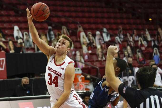 Wisconsin's Brad Davison shoots past Rhode Island's Jeremy Sheppard during the first half of an NCAA college basketball game Wednesday, Dec. 9, 2020, in Madison, Wis. (AP Photo/Morry Gash)