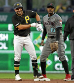 Pittsburgh Pirates' Francisco Cervelli, left, celebrates as he stands on second base, next to Arizona Diamondbacks' right fielder Adam Jones (10), after driving in a run with a double off Diamondbacks starting pitcher Luke Weaver in the second inning of a baseball game in Pittsburgh, Tuesday, April 23, 2019. (AP Photo/Gene J. Puskar)