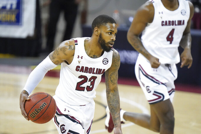 FILE - In this March 2, 2021, file photo, South Carolina guard Seventh Woods (23) dribbles during the first half of an NCAA college basketball game against Arkansas in Columbia, S.C. Woods has entered the NCAA transfer portal with the intention to play his sixth and final season elsewhere. A team spokesperson confirmed Wednesday, June 2, 2021, of Woods' intention to leave the South Carolina program.  (AP Photo/Sean Rayford, FIle)
