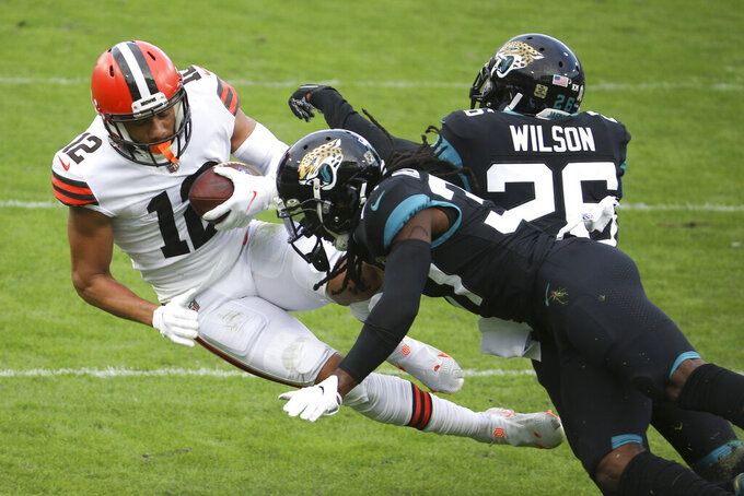 Cleveland Browns wide receiver KhaDarel Hodge (12) is stopped after a reception by Jacksonville Jaguars safety Jarrod Wilson (26) and cornerback Tre Herndon, center, during the first half of an NFL football game, Sunday, Nov. 29, 2020, in Jacksonville, Fla. (AP Photo/Stephen B. Morton)