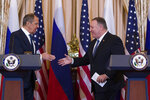 Secretary of State Mike Pompeo, right, reaches to shake hands with Russian Foreign Minister Sergey Lavrov, after a media availability at the State Department, Tuesday, Dec. 10, 2019, in Washington. (AP Photo/Alex Brandon)