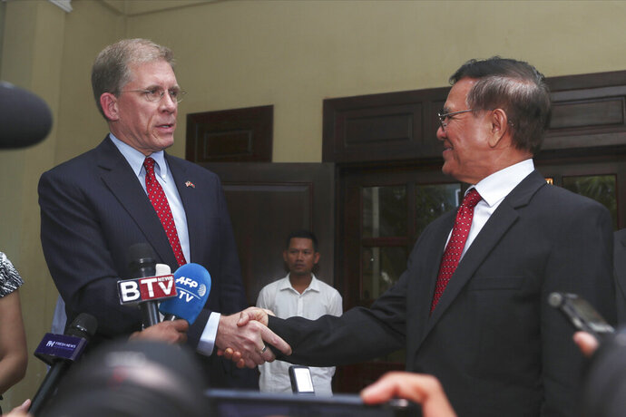 U.S. Ambassador to Cambodia W. Patrick Murphy, left, shakes hands with Cambodia National Rescue Party's President Kem Sokha after a welcoming meeting at his house in Phnom Penh, Cambodia, Monday, Nov. 11, 2019. A Cambodian court has lifted some restrictions on detained opposition leader Kem Sokha, essentially ending his house arrest. (AP Photo/Heng Sinith)