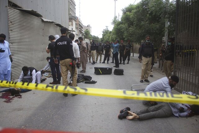 ED'S NOTE: GRAPHIC CONTENT - Security personnel examine the bodies of terrorists outside the Stock Exchange Building in Karachi, Pakistan, Monday, June 29, 2020. Gunmen attacked the stock exchange in the Pakistani city of Karachi on Monday. Special police forces deployed to the scene of the attack and in a swift operation secured the building. (AP Photo/Muhammad Ikram Suri)