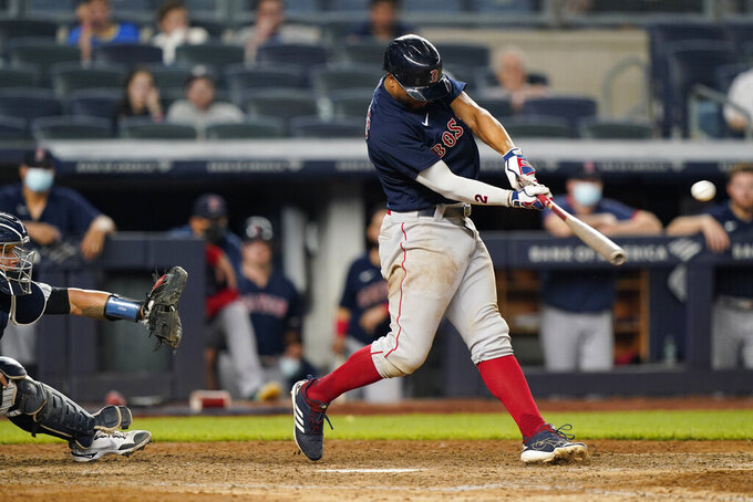 Boston Red Sox's Xander Bogaerts hits a two-run single during the 10th inning of a baseball game against the New York Yankees, Sunday, June 6, 2021, at Yankee Stadium in New York. Yankees catcher Gary Sanchez (24) is behind the plate. (AP Photo/Kathy Willens)